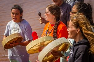 Michelle Paul, 2nd from left, sang and drummed along the banks of the Shubenacadie River on Sunday/Photo by Stephen Brake