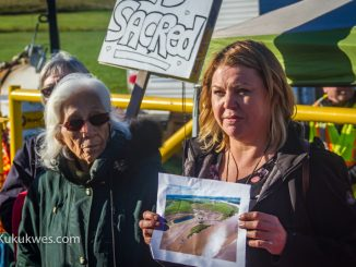 Cheryl Maloney, right, holds up a picture showing the Alton Natural Gas Storage Project site during a news conference Sept. 26/Photo by Stephen Brake